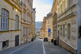 Fototapeta Uliczki - Scenic view of narrow street of Karlovy Vary - small ancient touristic resort town near the border between Czech Republic and Germany. Beautiful summer sunny look of famous town among hills in Czechia
