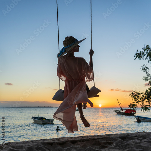 beautiful-girl-in-a-straw-hat-and-pareo-swinging-on-a-swing-on-the-beach-during-sunset-of-zanzibar-island-tanzania-africa-travel-and-vacation-concept