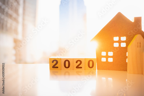 Wooden house with wood number 2020 on blurred city scape and copy space for text using as background business investment, new year, real estate, property concept.