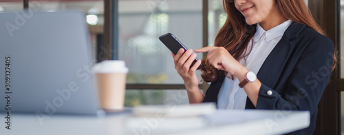 Obraz Closeup image of a businesswoman using mobile phone in office - fototapety do salonu