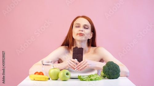 Satisfied anorexic girl greedily eats chocolate Wallpaper Mural