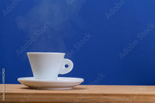 Fototapeta black coffee in a coffee cup from above isolated on wooden background. with clipping path. obraz na płótnie
