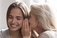 Two Generations Of Women Laugh Gossiping At Home