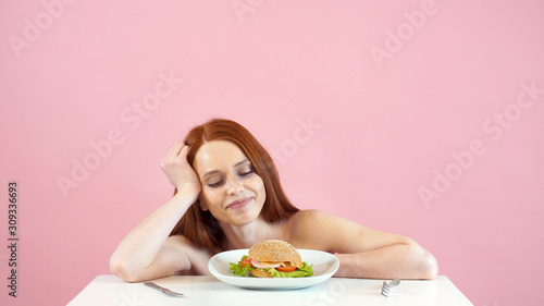 anorexic girl struggles with the temptation to eat a Burger. Canvas Print