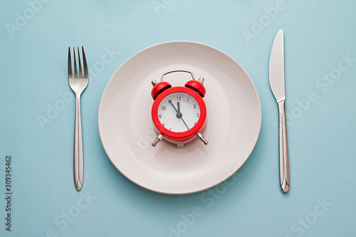 Photo Red alarm clock on a clean white dinner plate