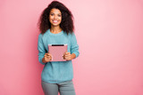 Portrait of her she nice-looking attractive lovely charming pretty cheerful cheery wavy-haired girl holding in hands tablet working remotely isolated over pink pastel color background
