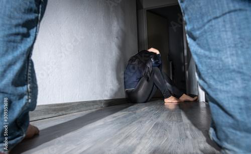 Femme battue assise dans un couloir Fototapet
