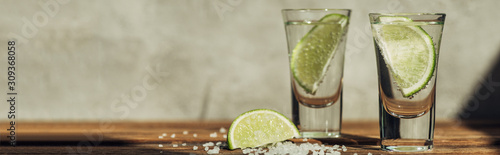 Photo fresh tequila with lime and salt on wooden surface in sunlight, panoramic shot