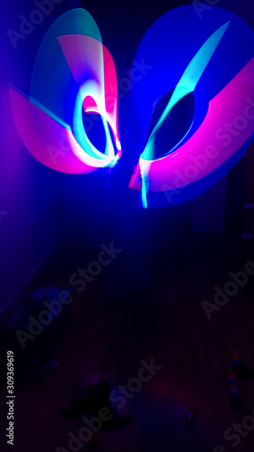Boy playing in his room with lightsaber in various colors Fototapet