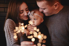 Portrait Of Happy Family, Mom, Dad And Baby Girl With Sparklers In Front. Family In Anticipation Of Christmas. Selective Photo.