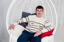 Stylish, Handsome Man Sitting In White Chair