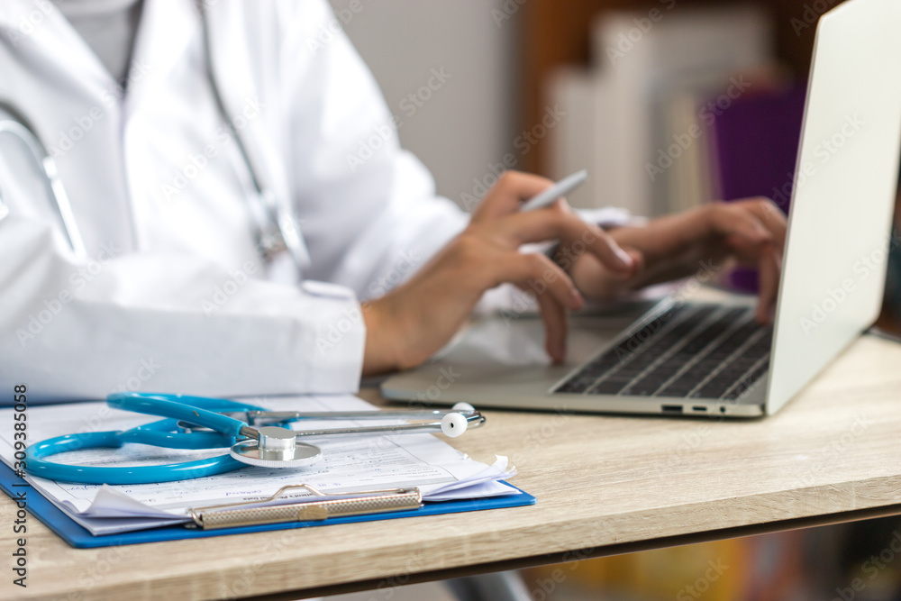 Fototapeta Medicine doctor hand explaining for patient at consulting room, working on laptop computer on desk in clinic, Focus stethoscope on foreground table in hostpital. Healthcare and medical concept.