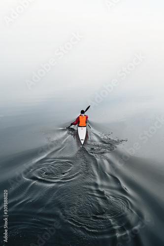 Fotografie, Obraz Man in a kayak paddling on a calm lake in winter