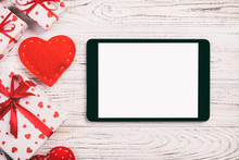 Digital Tablet Blank Screen With Gift Box And Hearts Decor On Wooden Table. Top View. Valentines Day Concept Background