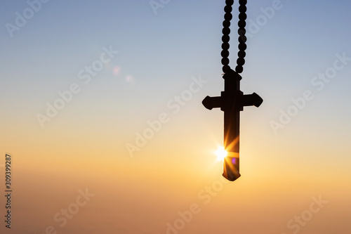 Foto Silhouettes of crucifix necklace symbol with bright sunbeam on the colorful sky