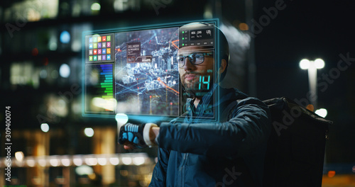 Portrait of an young delivery courier with bicycle is touching a futuristic screen with augmented reality hologram maps to view the addresses of customers in the evening in a city center Canvas Print