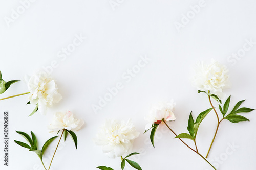 Flat lay pattern with white peonies on a white background