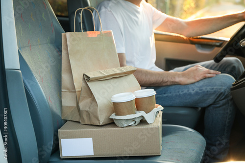Leinwand Poster Blank box, coffee cups, paper packages and courier in car