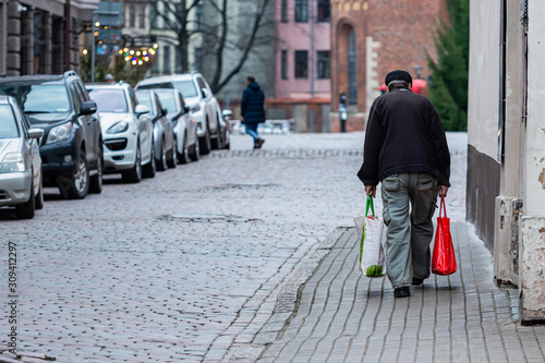 plakat Along the paved streets of the old town go old man with bags. Rear view