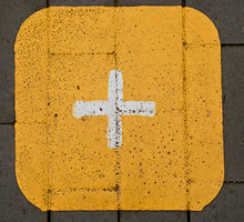 Painted   Plus Sign On A Pavement Yellow Background