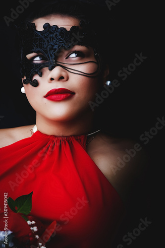 oung asian woman wearing an intricate black mask, deeply bright red lipstick on her lips of which is matching her vibrantly red dress, her eyes averting from the camera Canvas Print