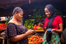 African Woman Shopping Food Stuff In A Local Market Paying By Doing Mobile Transfer Via Phone For A Trader