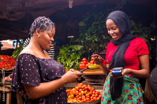 Photo African woman shopping food stuff in a local market paying by doing mobile trans