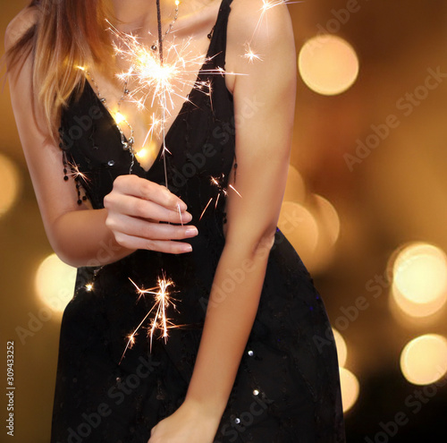 Young girl in evening dress holds a burning sparkler on a blurry gold background Fototapeta