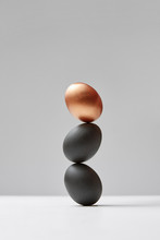 Vertical Column From Colored Eggs Black And Golden On A Gray Background. Easy Enrichment Concept.
