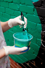 Close Up Of Anonymous Hands Painting A Mural On A Brick Wall