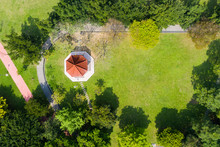 Red Gazebo And Trees On Green Grassland In Park, Aerial View.