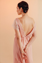 Back View Portrait Of Young Woman With Bun Hairstyle Wearing Stylish Clothes