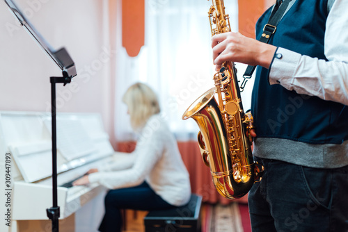 Fotomural Student saxophone at a lesson in a music school close-up on background of a teac