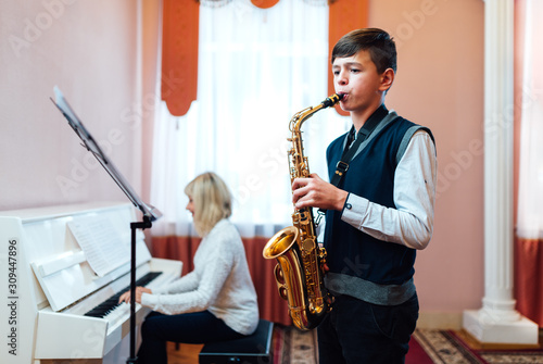 Fototapeta A teenage boy learns to play saxophone in a music lesson to accompaniment of a female teacher on the piano