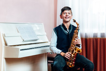 Cheerful Student Boy Sitting With Saxophone Before Music Lesson