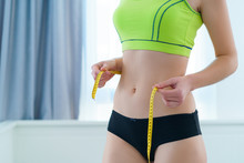 Healthy Sport Fitness Slim Woman Measuring Her Thin Waist With A Tape Measure For Showing Weight Loss And Diet Results. Motivation And Progress In Slimming, Achieving Weight Loss Goals