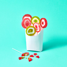 Broken Lollipop And Cardboard Box With Multi-colored Lollipops On A Blue Background With Space For Text
