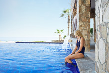 Woman On Edge Of Swimming Pool Dipping Feet Into Water