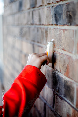 Valokuva Child hand on doorbell at brick home