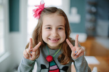 Cute Young Girl Showing The Peace Sign With Her Hands