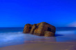 canvas print picture - Ruins of a coastal building washed away by the sea on a starry night.