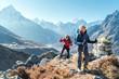 Leinwandbild Motiv Couple following Everest Base Camp trekking route near Dughla 4620m. Backpackers carrying Backpacks and using trekking poles and enjoying valley view with Ama Dablam 6812m peak