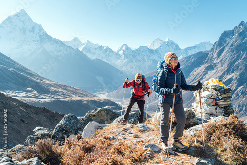 Fototapeta Couple following Everest Base Camp trekking route near Dughla 4620m. Backpackers carrying Backpacks and using trekking poles and enjoying valley view with Ama Dablam 6812m peak obraz