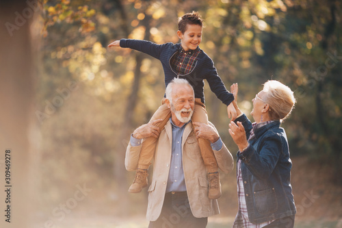 Fotomural Grandparents having a lovely autumn day with their grandson in nature