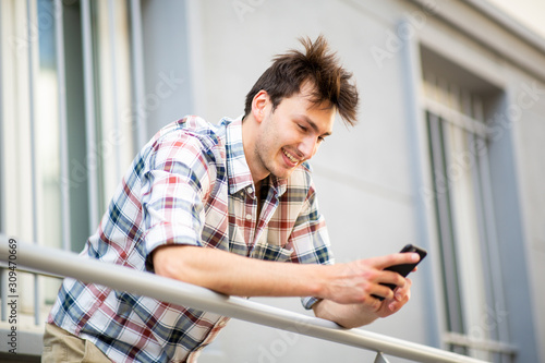 Photo smiling young man on balcony looking at cellphone