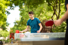 Young Man Playing Table Tennis In Park