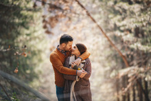 Young Caucasian Couple Hugging And Looking Each Other With Love While They Are Standing In Forest.