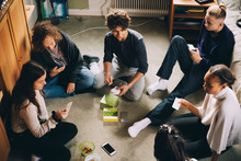 High Angle View Of Male And Female Friends Playing Board Game While Sitting In Bedroom At Home