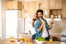 Two Attractive Caucasian Male And Female Friends Enjoying In Cooking, Dancing And Singing In The Kitchen.