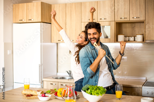 Obraz na plátně Two attractive Caucasian male and female friends enjoying in cooking, dancing and singing in the kitchen